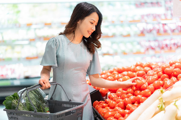 The young girl is choosing to buy vegetables at the supermarket